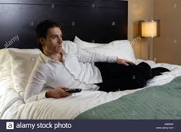 tv bed pillow young man with a remote control lying alone on a bed and watching tv