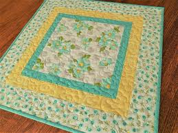 quilted square table toppers bright and cheery this quilted square table topper features aqua