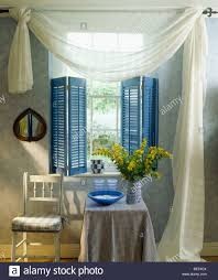 white voile drapes and blue plantation shutters on window in