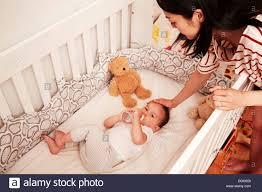 Baby Sleeping In A Crib baby boy lying in crib drinking baby bottle stock photo royalty