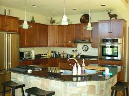 curved beige kitchen island with black granite top and sink
