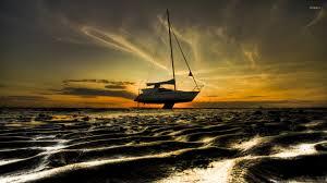 Sailboat Wallpaper Sailboat On A Sunset Sandy Beach Wallpaper Photography