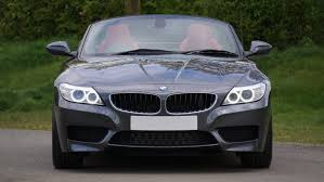 black convertible bmw black bmw convertible in front of green bushes free stock photo