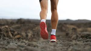 runner man tying running shoes and runs on trail outdoors fit