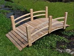 small garden bridge rustic wooden bridge deisgn in green garden with narrow water