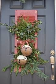 this christmas door decor with bells and an old shutter is just so