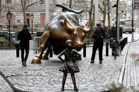little statue stands up to iconic wall street bull and