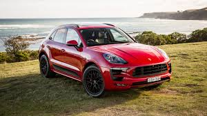 red car porsche macan 2017 on the background of the ocean