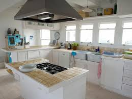 white beige tile countertop light brown wooden cabinets tile