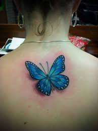 blue ink butterfly tattoo on upper back