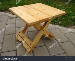 small wooden folding camp stool close stock photo 34395337