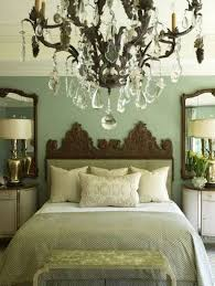 bedroom with sage green warm paint colors and crystal chandelier