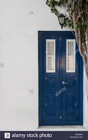 a blue front door on a white greek house with a vine growing