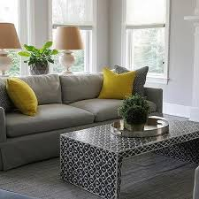 gray sofa with bright yellow pillows and black waterfall coffee