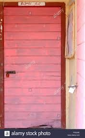 pink painted padlock closed wooden doors on the mustard colored