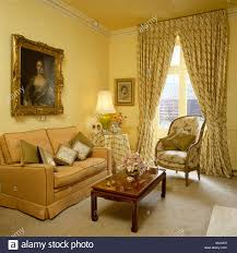 large portrait above peach sofa in pale yellow livingroom with