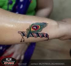 peacock feather with flute tattoo on forearm