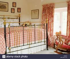 Country Bedroom by Red Checked Bedlinen On Antique Brass Bed In Country Bedroom With