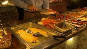Buffet With Crab Legs by An Asian Man Collects Food Quickly At A Buffet Lunch In Indian