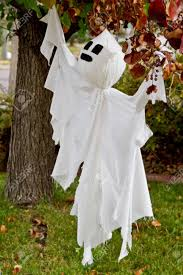 halloween ghost hanging in tree in yard for decoration stock photo