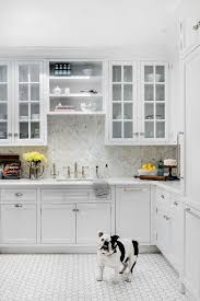 white kitchen cabinets with hexagon backsplash adding a warmer tone into this all white kitchen with