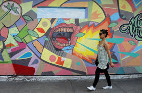street art caminando peru y bolivia a woman is walking past a mural on a wall an open mouth is yelling