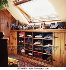 pictures of velux window above clothes on open shelves in attic