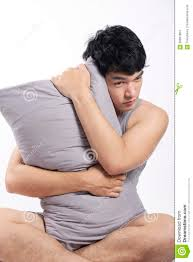 asian man in grey pajamas sitting and holding the pillow stock