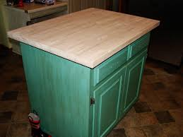 small square green painted kitchen island with butcher block