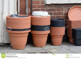 stacks of plastic flower pots for sale outside shop stock photo