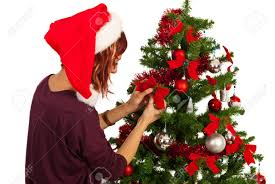 woman with santa hat decorate christmas tree with red ribbons