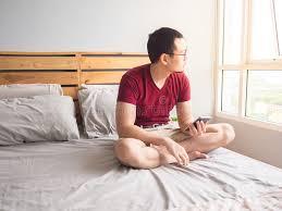 dans sa chambre homme seul jouant le sien téléphone dans sa chambre à coucher image