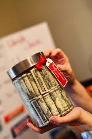 gifts for someone turning 60 fifty one dollars bills rolled up and stacked inside a clear jar