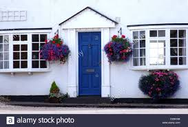 blue front door of a cottage painted white with hanging baskets