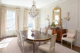 oval french dining table with gold trim and gray linen square back