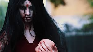 cosplayer in scary halloween of in bloody red dress alma