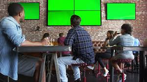 friends watching game in sports bar on screens shot on r3d stock