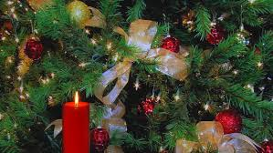 Decorate Christmas Tree Ribbon Video by Glowing Golden Holiday Candle With Blinking Christmas Tree Lights
