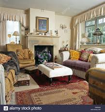 Cottage Rugs Sofas Piled With Cushions On Either Side Of Upholstered Stool In