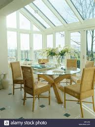 high back wicker chairs and glass table in modern conservatory