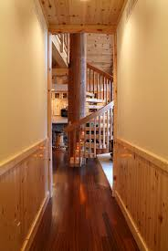 hallway with vertical knotty pine paneling and spiral staircase