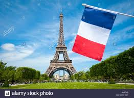 Paris Flag French Flag Flying In Bright Blue Sky In Front Of The Eiffel Tower