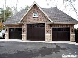 three dark brown coloring of garage doors with brick wall exterior