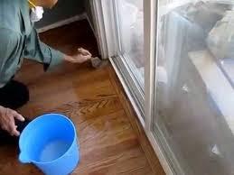 applying coat of water based polyurethane on hardwood floor