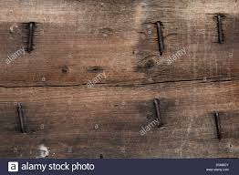 a stained pine board shows its age with rusty nails and splitting