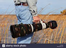 Professional Photographer Professional Photographer Carrying A Camouflaged Canon Stock