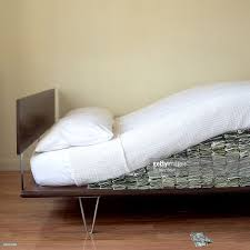 money hidden under modern bed mattress stock photo getty images