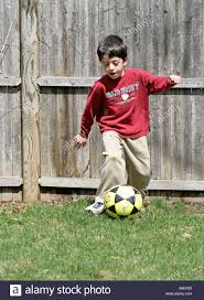 a young boy playing soccer ball in his parents backyard stock