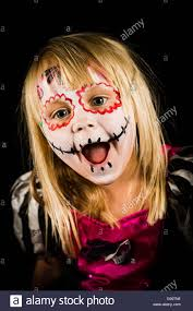 a young with scary face paint and a pumpkin lantern at