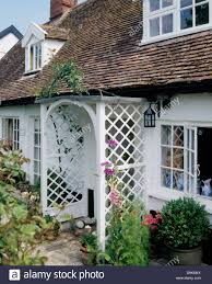 white 16th century cottage with trellis porch and dormer windows
